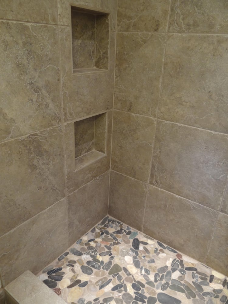 "18""x 18"" porcelain tile on the walls with flat river rocks ..."