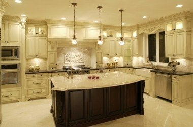 White kitchen cabinets with dark island cabinets and granite counter