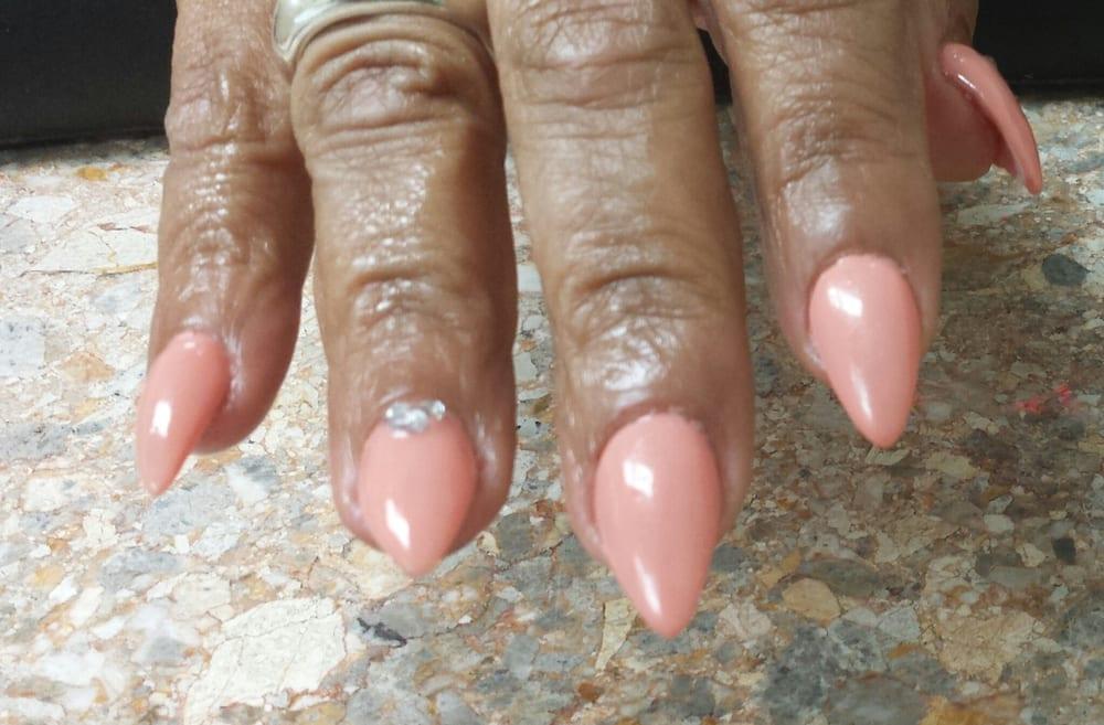 States. Stiletto shaped acrylic nails with gel polish and rhinestones