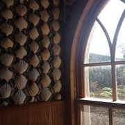 A little house decorated in a shells and pine cones.