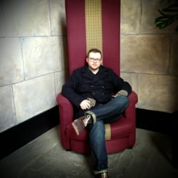 Sitting in one of the giant chairs near the hotel entrance.