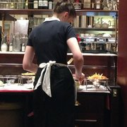 Über friendly server prepping the second part to the meal