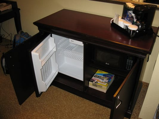 A Cabinet Opens To Reveal This Mini Fridge And A Microwave