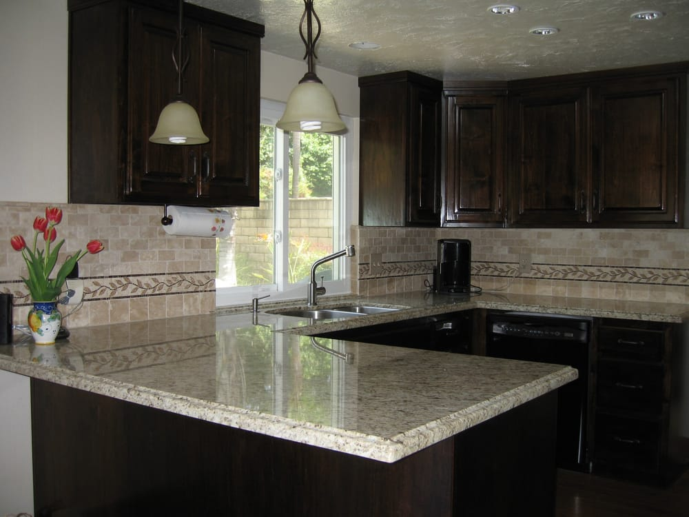 dark brown cabinets and giallo santo granite counter tops travertine