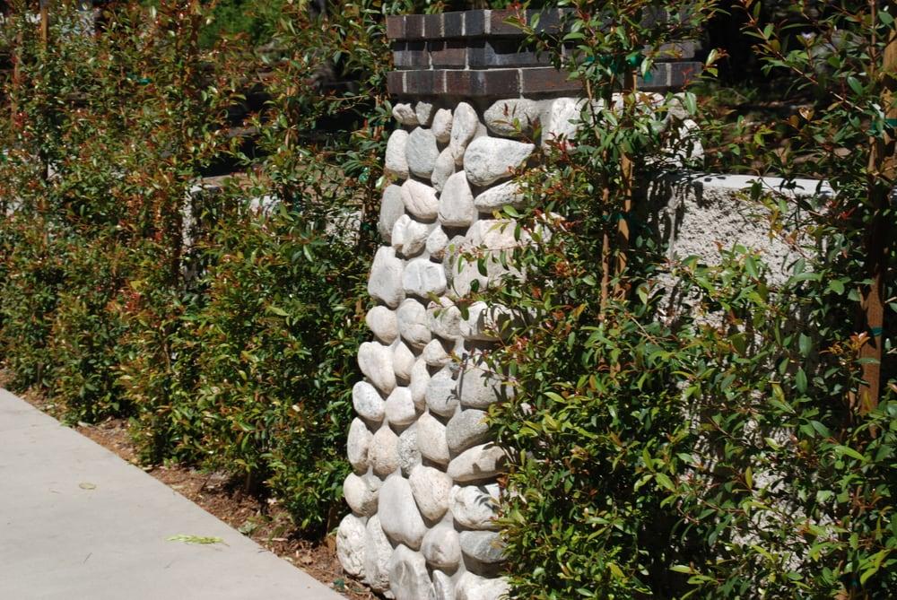 River rock veneered columns make a statement between for River rock columns