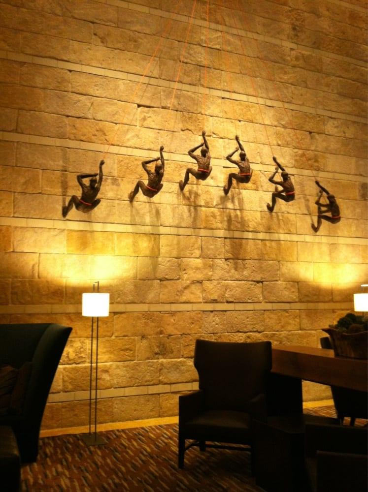 Climbing men piece of art hanging on the side of the wall by the ...