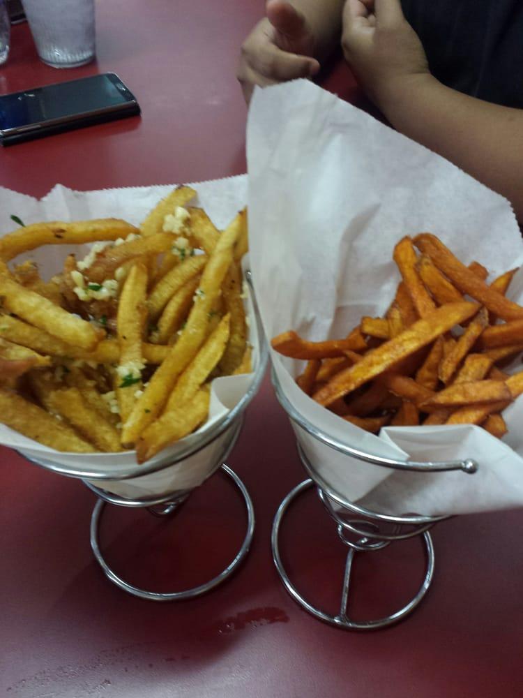 Garlic truffle fries and sweet potato fries, both are half ...