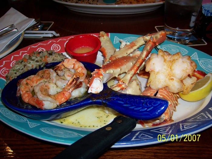 Oven baked lobster tail, steamed crab legs and garlic shrimp served with over buttered wild rice ...