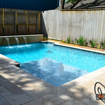 Geometric swimming pool with tanning ledge, bubblers, water ...