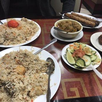 Photo of Haat Bazaar - Jackson Heights, NY, United States. Chicken biryani (left), chicken korma (small bowl), salad, chicken kebab, and shami kebab (far right)