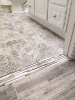 Mosaic transition between gray wood-look porcelain tile and brick ...