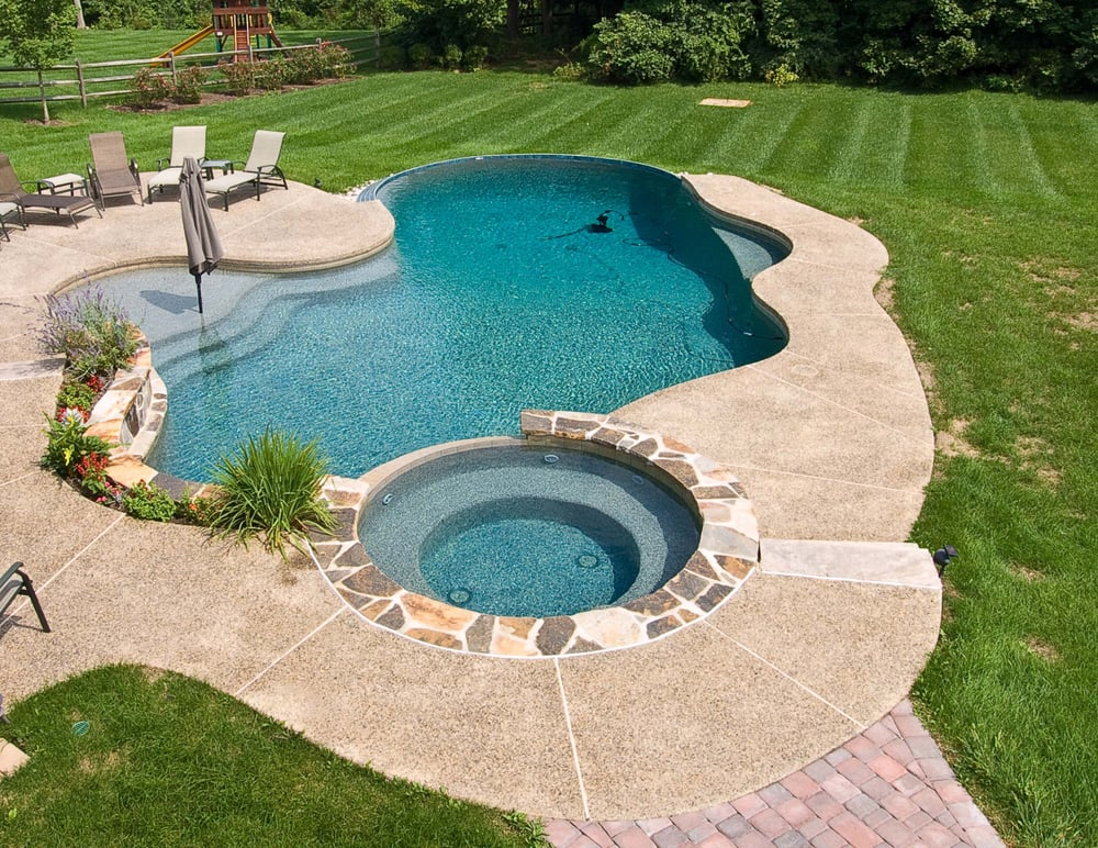 Beautiful pool with faux edge sun shelf with umbrella for Pool edges design