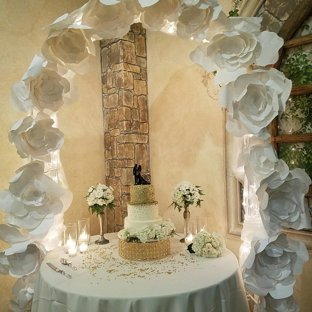 Wedding cake table with paper flower arch - Yelp