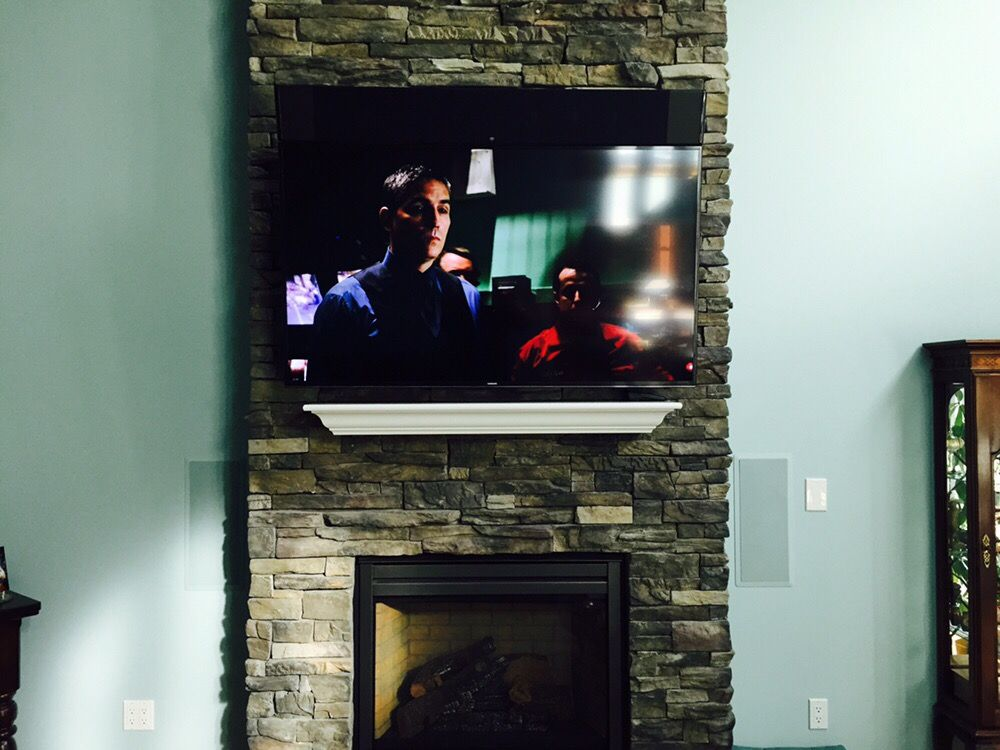 TV over stone fireplace with TV mounted center channel speaker ...