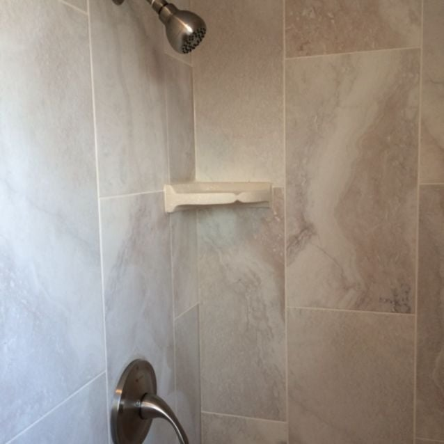 "New shower stall with 12 x 24"" porcelain tiles a corner"