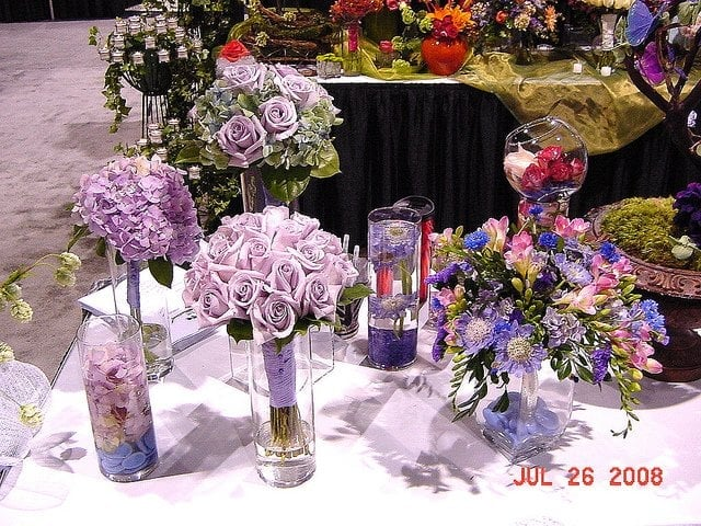 An ensemble of bouquets and centerpieces in purples flowers include hydrangea roses for Village gardens blue springs mo