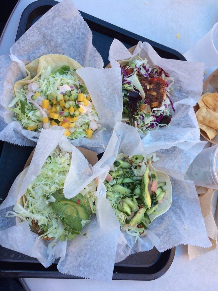 Clockwise from top left: fresco taco, fried fish taco, spicy ahi tuna taco, and calamari taco ...