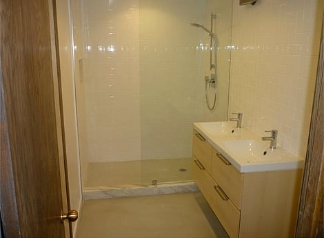 Bathroom includes tiled walls and a semi-enclosed shower with a ...