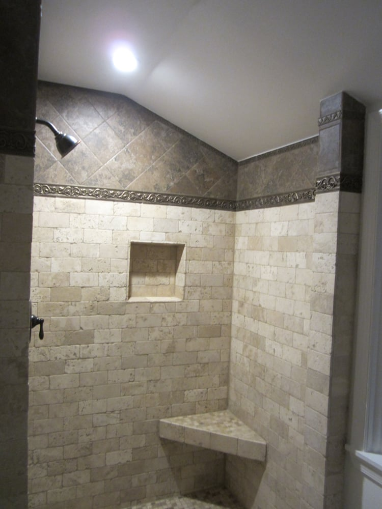 Tumbled marble shower with floating corner bench and tile niche ...