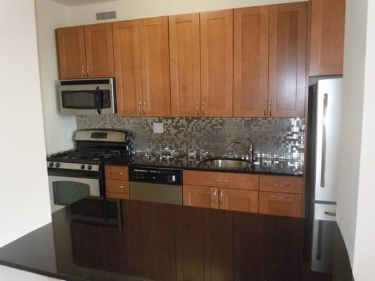 3x6 Slate Tile kraftmaid walnut cabinets. Stainless backsplash. Black ...