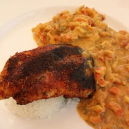 ... . Blackened Catfish with crawfish creole sauce over a bed of rice