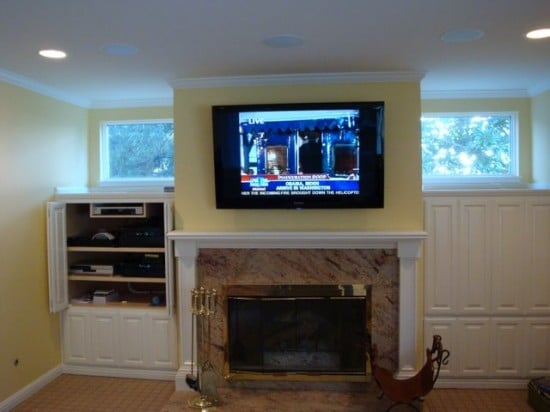 Tv Mounted Above A Fireplace Wires Hidden Components Located Off To The Side Within Cabinet