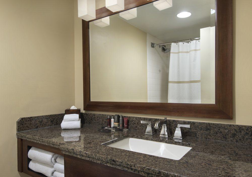 Sleek Modern Guest Bathrooms Boast A Granite Vanity And THANN - Bathroom vanities overland park ks