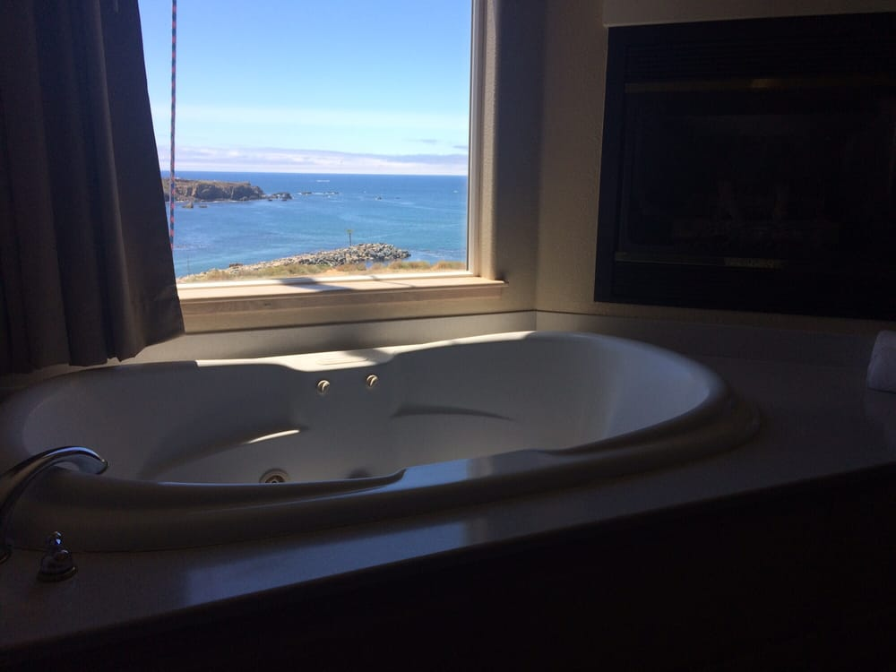 Huge bathtub, fireplace overlooking the water with big robes waiting ...