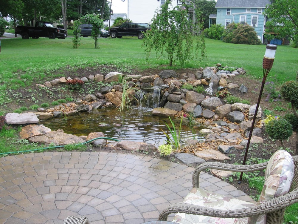 Aqua scape koi pond water fall next to ideal millstone for Koi pond maintenance near me