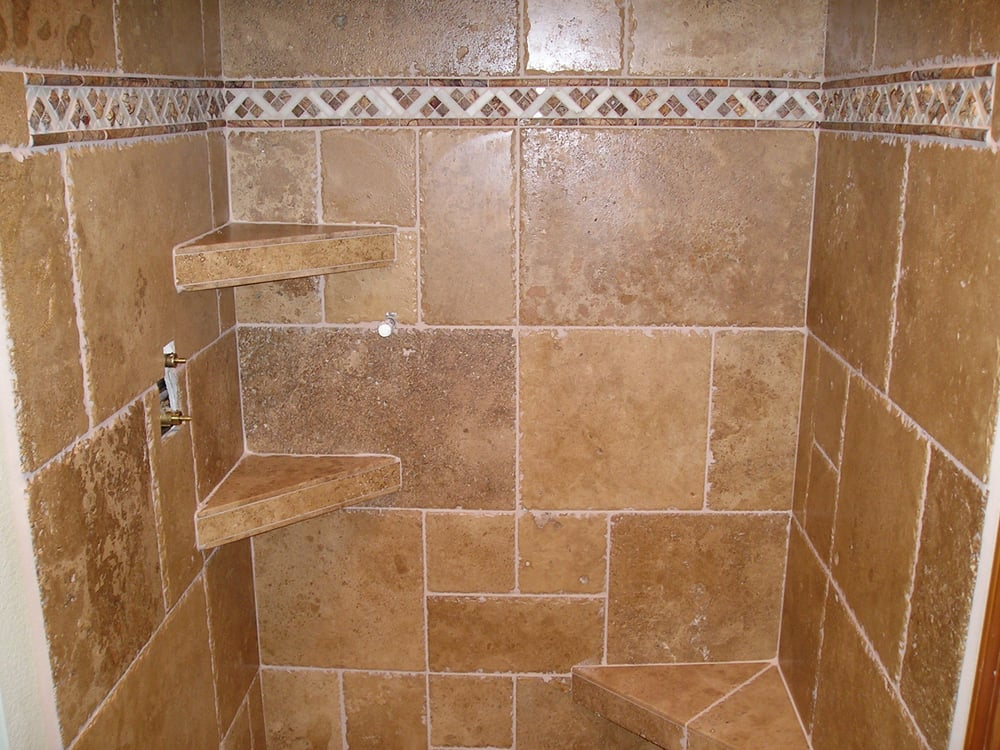 Stone tile shower with a bench and two shelves. These benches will ...