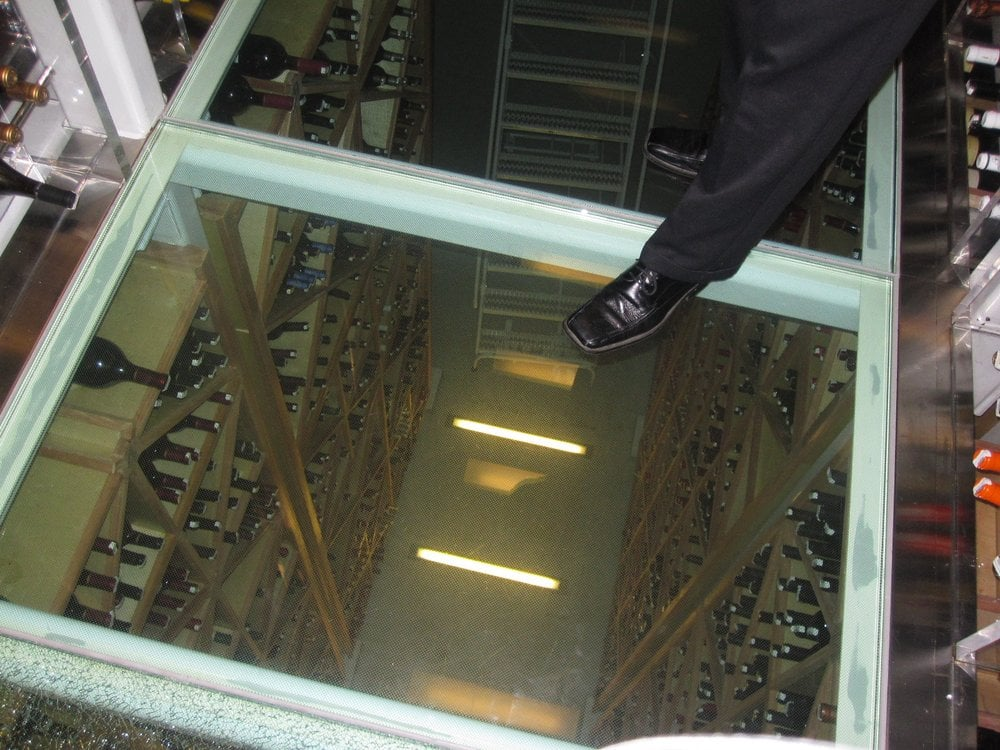 Glass floor looking below into ground floor of wine cellar for Wine cellar in floor