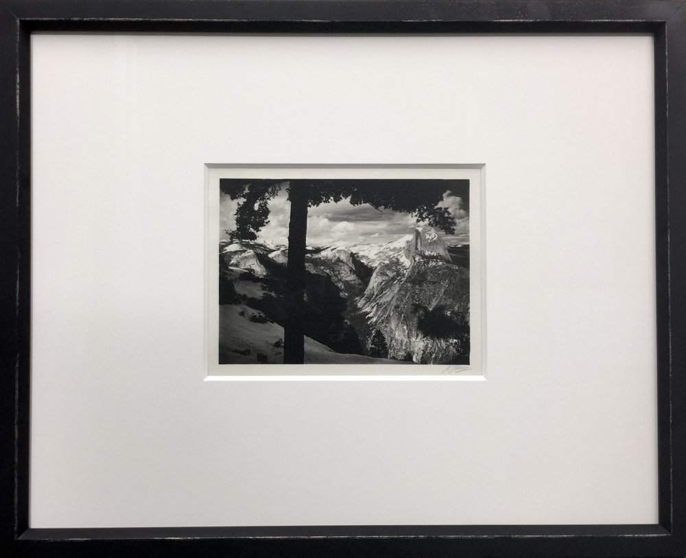 An original signed Ansel Adams fit with a simple black rustic frame ...