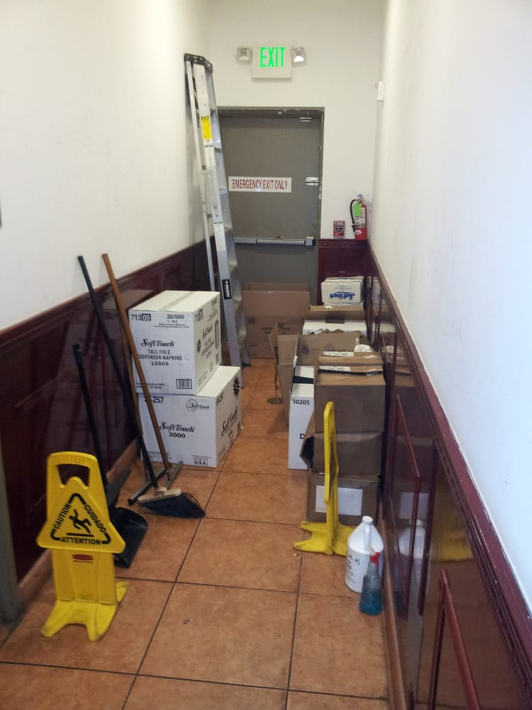 Closer-up view of the mostly-blocked hallway leading to the marked fire escape back door, a fire ...