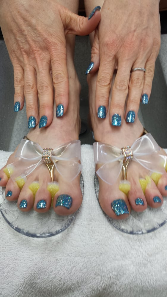 Acrylic nails with blue polish base and glitters polish top and ...