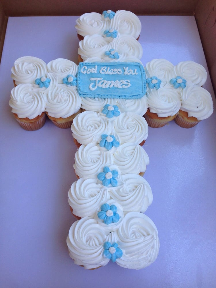 Vanilla cupcakes with buttercream frosting in a cross ...