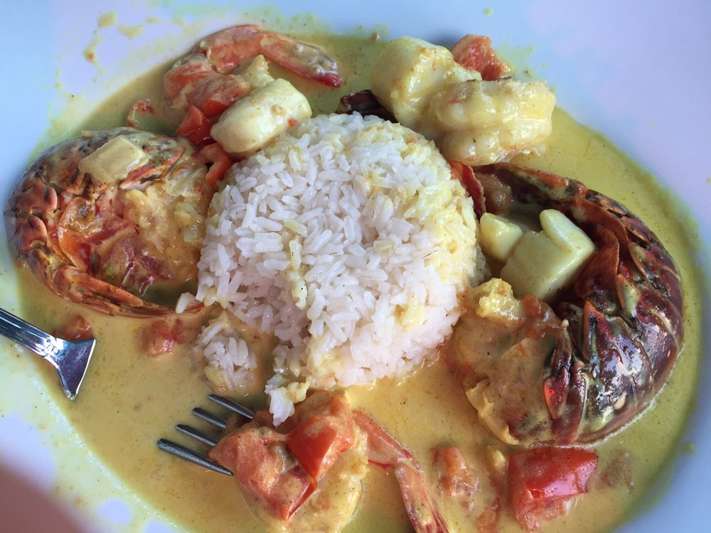 Seafood dish lobster tail scallops shrimp in a coconut cream broth with coconut rice yum Cuban restaurant garden city ny